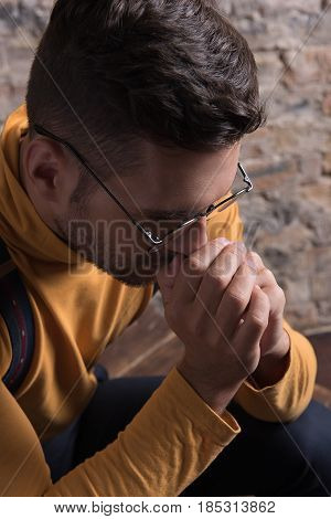 Feeling hopeless. Depressed young guy with stubble sitting alone and touching his face. Top view