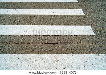 Close-up image of asphalt road and white zebra pedestrian crossing