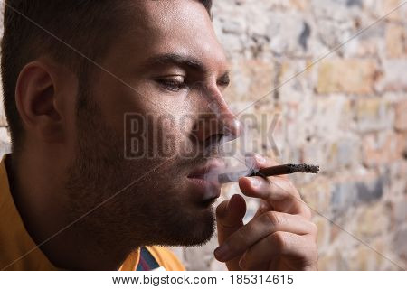 Satisfaction. Close up portrait of smoking guy looking down contentedly. Brick wall in the background