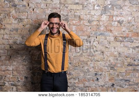 Always in trend. Stylish young man standing against brick wall. He looking at camera with smile and touching his eyeglasses. Copy space in right side