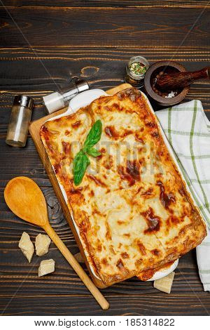 Lasagna in baking dish isolated on wooden background