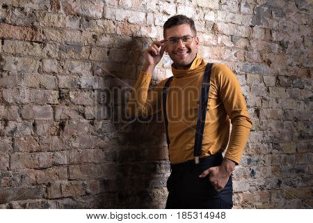 Happy life. Young fashion man sensually touching his glasses while holding his other hand in his pocket. He looking at camera joyfully