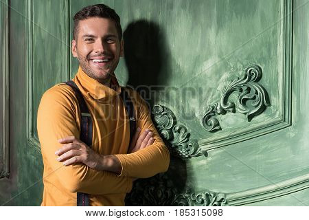 Walk through life with smile. Waist up portrait of cheerful man standing and smiling. He is looking at camera positively. His arms crossed with happiness