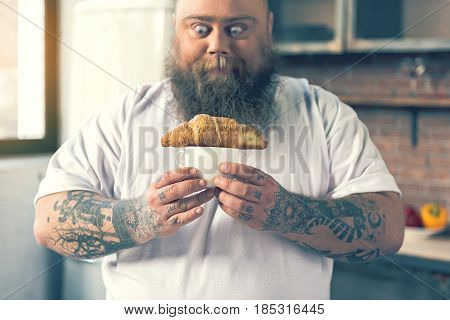 Fat bearded man is staring at pastry on cup of coffee with shock and hunger. He is standing in kitchen. Focus on breakfast