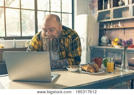 Joyful thick guy is watching something on laptop while having breakfast in kitchen. He is leaning on table and smiling