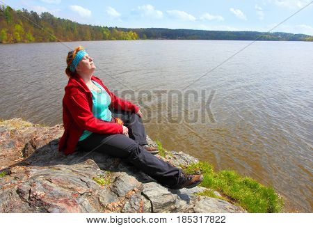 Overweight hiker woman relaxing and meditating on a cliff over lake. Active lifestyle and mental health theme.