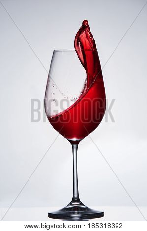 Splashing and moving red wine in the pure wineglass standing against light background with reflection on the stand. Brightly wine and elegant goblet. Concept of the luxury lifestyle. Vertical photo. Sommelier and tasting.
