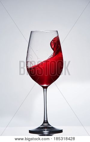 Red wine splash in the delicate elegant wineglass standing against light background. Mowing wine in the pure goblet. Concept of the luxury lifestyle. Vertical photo. Viticulture, grapes and winery. Natural drink.