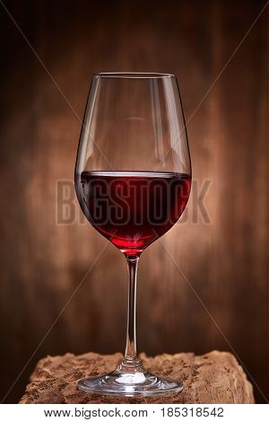 Fragile goblet of the red wine on the wooden stand on wooden wall background. Celebration and relaxation. Concept of the luxury lifestyle. Viticulture, grapes and winery. Natural material and drink. Vertical photo.