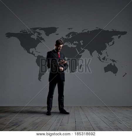 Businessman standing with smartphone. World map background. Business, globalization, concept.