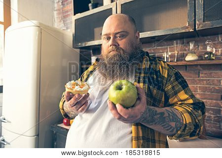 This is not food. Shock fat man is looking at apple with aversion. He is standing in kitchen and holding sweet dessert