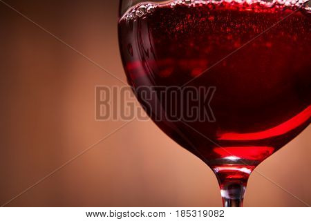 Elegant and fragile wineglass of tasty red wine against brown wooden background close-up. Horizontal photo and macro. Concept of the luxury lifestyle. Sommelier and tasting. Natural drink. Viticulture and winery.