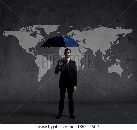 Businessman with umbrella standing over world map background. Business, risk, insurance, concept.