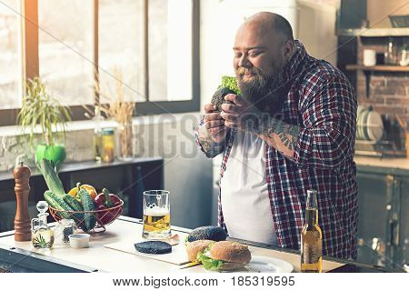 Happy fat man is eating fast food at home. He is smelling sandwich with pleasure and smiling