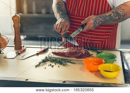 Close up of male hands sharpening knives before cutting meat