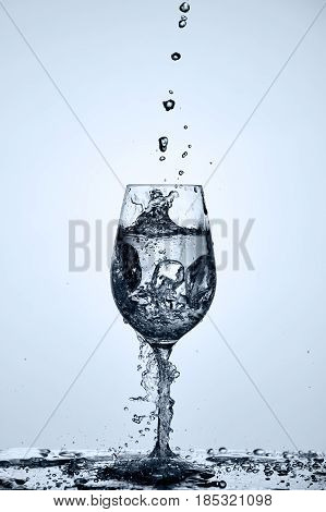 Drinking transparent water is poured into a wineglass standing on the glass with water splashing against light background. Useful and natural product. Care for the environment and ecology. Concept of the healthy lifestyle.