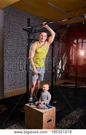 Smiling young father and little son standing on the box against brick wall at the cross fit gym. Father and son in the sportwear and sportive shoes. Vertical photo. Rearing children in the healthy lifestyle.