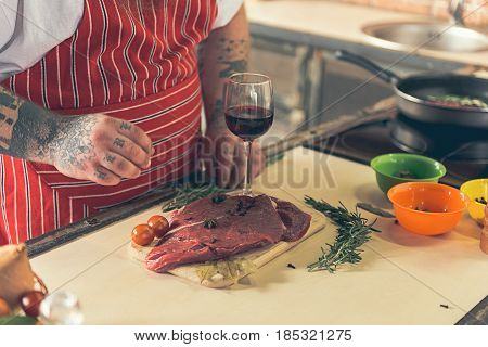 Close up of male arms adding sault to meat. Focus on raw meat and glass of wine on wooden board
