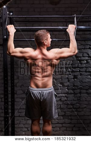 Rear view photo of the young muscular male doing exercises on horizontal bar against brick wall at the cross fit gym. Sportsman withot a shirt, but in the sportive shorts. Power and energy, body and muscle. Healthy lifestyle.
