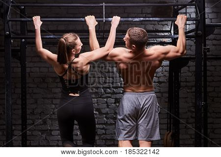 Rear view photo of the young muscular sporty man and woman doing exercises on horizontal bar against brick wall at the cross fit gym. Sporty couple in the sportwear. Power and energy, body and muscle. Healthy lifestyle.
