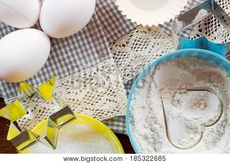 Baking ingredients on a lace cloth: eggs flour in a bowl with a heart shape cookie cutters. Top view flat lay