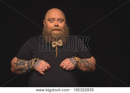 I am your teddy bear. Excited fat man is standing and posing with little bow on his bearded hair. He is looking at camera with joy. Isolated