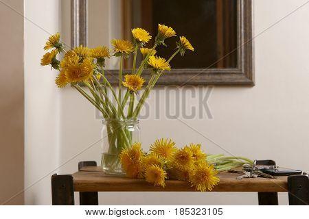 Dandelions in glass jar.  A bouquet of dandelions. Yellow wild flowers in entryway.