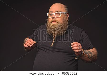 Waist up portrait of pensive fat man with glasses posing and gesturing by hands. Isolated on black background