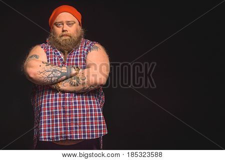 Portrait of confident fat male hipster standing with crossed arms. He is looking at camera with seriousness. Isolated and copy space in right side
