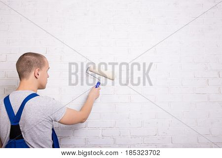 Back View Of Young Man Painter In Workwear Painting Brick Wall With Paint Roller And Copy Space