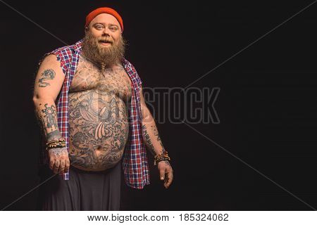 Portrait of happy fat male hipster standing with bare large belly. He is looking at camera and laughing. Isolated. Copy space in right side