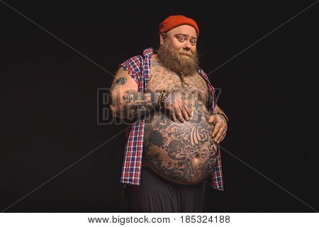 I am proud of my belly. Joyful fat man is touching his naked abdomen with tattoos and smiling. Isolated on black background