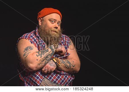 Portrait of shy fat man hiding his large abdomen by shirt and hands. He is standing and looking at camera playfully. Isolated and copy space in right side