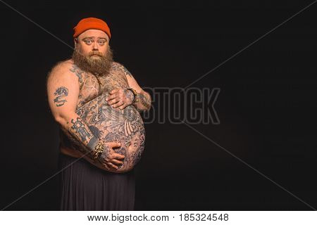 Portrait of innocent fat man touching his big naked tummy with love. He is standing and looking at camera. Isolated and copy space in right side