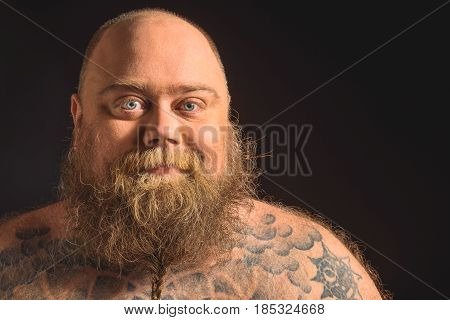 Portrait of happy fat nude man with tattoo on his body and large beard. He is standing and smiling. Isolated and copy space in right side