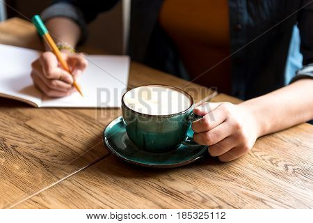 close up female arm with mug of hot beverage. She writing in copybook at table in apartment