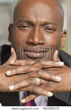 Serious African American man with hands clasped