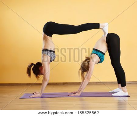 Two athletes doing yoga on purple rug in gym