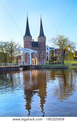 Delft, Netherlands - April 8, 2016: Colorful Oostpoort or Eastern Gate domes, canal and house reflection, Delft, Netherlands, Holland against blue sky