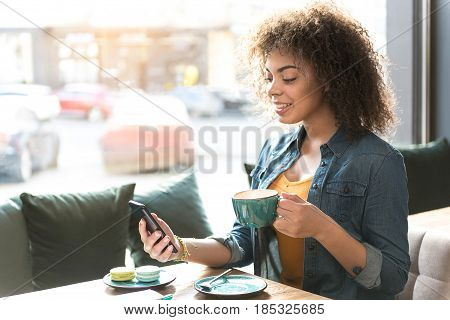 Side view of beaming mulatto female looking at cellphone while drinking cup of coffee in confectionary shop
