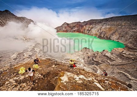 EAST JAVA,INDONESIA-DEC 11:Unidentified miner harvests raw sulphur from the crater of Kawah Ijen volcano in hazardous working environment in Kawah Ijen on Dec 11,2010 East Java, Indonesia