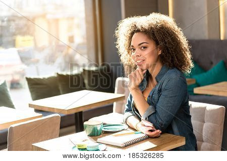 Portrait of african woman expressing thoughtfulness while locating at table in confectionary shop