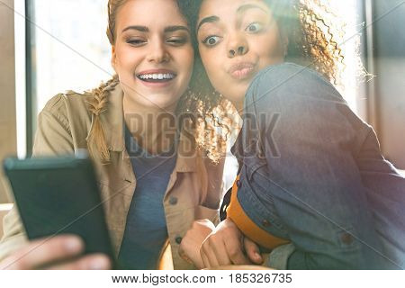Low angle happy mulatto girl taking selfie photo with friend by mobile. They looking at it