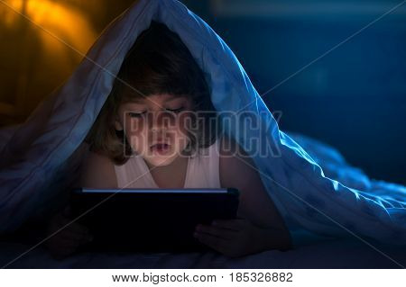 Close up of little boy watching cartoons on the digital tablet at night with copy space
