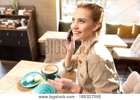 Top view of woman demonstrating cheerfulness while speaking at cellphone in confectionary shop