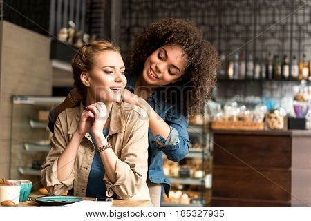 Happy african girl embracing cheerful female. They speaking with while she sitting at table