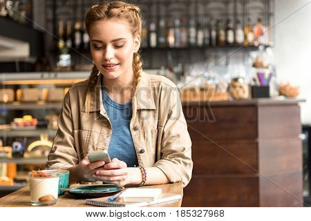 Woman expressing happiness while looking at mobile. She locating at desk in confectionary shop
