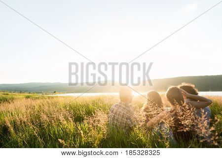 Friends sitting together at lake in summer enjoying sundown and evening mood