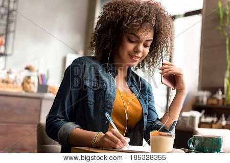 woman expressing happiness while hearing song. She noting in scribing-dairy while locating at table in cafe