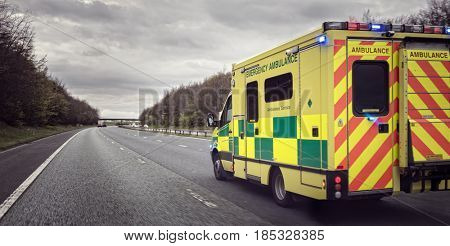 British ambulance responding to an emergency in hazardous bad weather driving conditions on a UK motorway